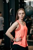 Beautiful athletic girl dressed in sporty clothes standing next to the sport equipment in the modern gym royalty free stock image
