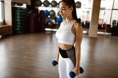 Beautiful athletic girl dressed in white sports top and tights holds dumbbells royalty free stock images