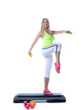 Beautiful athletic girl exercising with dumbbells. On stepper Royalty Free Stock Image