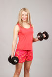 Beautiful athletic girl holding dumbbells Royalty Free Stock Photography