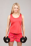 Beautiful athletic girl holding dumbbells Stock Photography