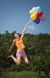 Beautiful and athletic Girl jumping with balloons Royalty Free Stock Photo
