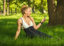 Beautiful athletic girl listening to music while sitting on the Stock Photo
