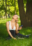 Beautiful athletic girl listening to music while sitting on the Royalty Free Stock Photo