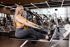 The beautiful athletic girl with long blond hair dressed in a sportswear is doing sport exercises with equipment on the stock images