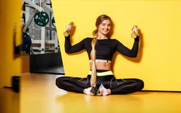 Beautiful athletic girl with long blond hair dressed in a stylish sportswear is sitting on the yellow floor next to the royalty free stock photo