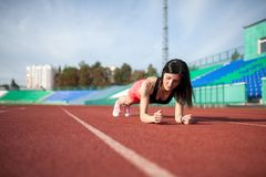 Beautiful and athletic brunette girl in in shorts and tank top push ups at the stadium. Beautiful and athletic girl push ups at the stadium royalty free stock image