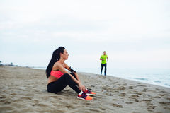 Beautiful athletic girl resting after exercise and her boyfriend running on the  sea side Royalty Free Stock Image