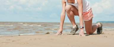 Beautiful athletic girl in a starting position. On the beach stock photos
