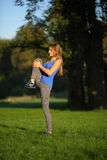 Beautiful athletic girl stretches the knee Stock Image