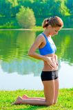 Beautiful athletic girl in the top and form rest at the lake Royalty Free Stock Images