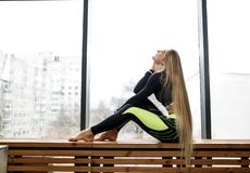 Beautiful athletic girl with very long blond hair is sitting on the wooden windowsill next to the panoramic windows in royalty free stock photography