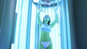Beautiful and athletic girl in a white bathing suit sunbathing in the solarium. stock footage