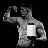 Beautiful athletic man holding a jar of sports nutrition Stock Image