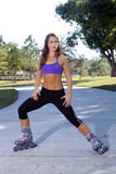 Beautiful Athletic Rollerblader Outdoors (2). A lovely young brunette with remarkable abdominal musculature rollerblades outdoors Stock Images