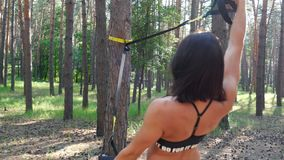 Beautiful, athletic, young woman, coach, instructor, performs exercises, doing exercises with fitness trx system. TRX suspension straps. In pine forest, in stock footage