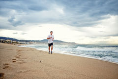 Beautiful athletic sportsman running along the beach on amazing sea and sky background. Morning jog, fitnes and healthily lifestyle, sport and health concept stock image