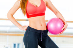 Beautiful athletic waist of a young girl with  pink ball in hand the gym Stock Image