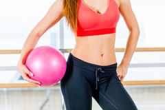 Beautiful athletic waist of a young girl with  pink ball in hand the gym Royalty Free Stock Images