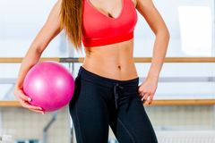 Beautiful athletic waist of a young girl with  pink ball in hand the gym Stock Images