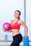 Beautiful athletic waist of a young girl with  pink ball in hand the gym Royalty Free Stock Photos