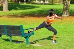 Beautiful athletic woman doing exercise in the park Stock Photos