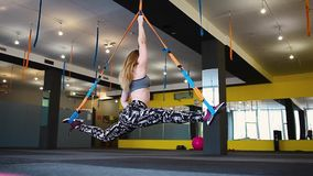 Beautiful athletic woman doing exercises using trx in sportswear at gym. Healthy lifestyle concept stock video footage