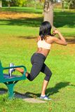Beautiful athletic woman doing sit ups exercise in the park Royalty Free Stock Image