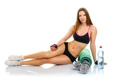 Beautiful athletic woman with dumbbells, mat for fitness, a bott Stock Photos
