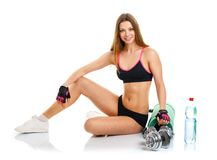 Beautiful athletic woman with dumbbells, mat for fitness, a bott Royalty Free Stock Photo