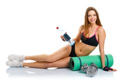 Beautiful athletic woman with dumbbells, mat for fitness, a bott Stock Photography
