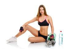 Beautiful athletic woman with dumbbells, mat for fitness, a bott Stock Photo