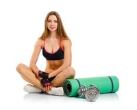 Beautiful athletic woman with dumbbells, mat for fitness sitting Stock Image