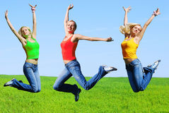 Beautiful athletic woman jumping. On a green meadow Stock Images