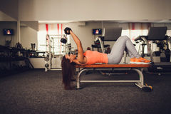 Beautiful athletic woman making exercise. Lying in gym Royalty Free Stock Photo