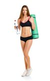 Beautiful athletic woman with mat for fitness and bottle of wate Stock Photos