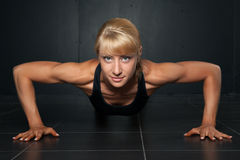 Beautiful athletic woman is pushed up. On  a dark background Stock Images