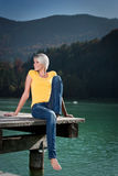 Beautiful athletic woman relaxing on a lake. Beautiful happy slender athletic young blond woman relaxing on a lake sitting with her legs dangling off a wooden Stock Photography