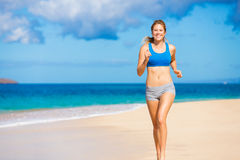 Beautiful Athletic Woman Running on the Beach Royalty Free Stock Photography