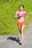 Beautiful athletic woman running in countryside Stock Photography
