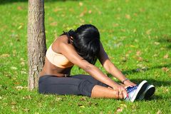 Beautiful athletic woman stretching after exercise in the park Stock Photos