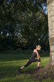 Beautiful athletic young adult woman is doing exercises outdoors in park Stock Images