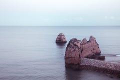 Beautiful Atlantic ocean view horizon with sandy beach, rocks and waves at sunrise. Algarve, Portugal Stock Photography