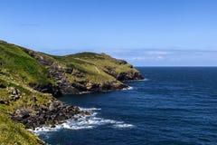 Beautiful Atlantic shore. Rocky atlantic coast of United Kingdom with green pastures and blue sky Royalty Free Stock Photos