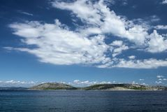 Island of Zmajan Orut , Adriatic Sea, Croatia. Beautiful atmosphere with white clouds and blue sky above island of Zmajan on Adriatic Sea, Dalmatia, Croatia royalty free stock photography