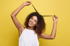 Beautiful attractive African American woman posting play with her curly afro hair. Yellow studio background. Copy Space. Beautiful attractive African American stock photo