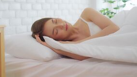 Beautiful Attractive Asian woman wearing Pajamas sleep close her eyes smile sleep and sweet dream on bed in bedroom