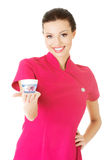 Beautiful attractive beautician holding a cream. Royalty Free Stock Photography