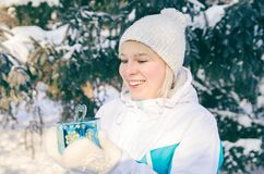 Beautiful attractive blonde girl rejoices in a box with a gift that is holding in her hands stock photography