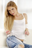 Beautiful and attractive blonde woman posing in blue jeans dress Stock Images